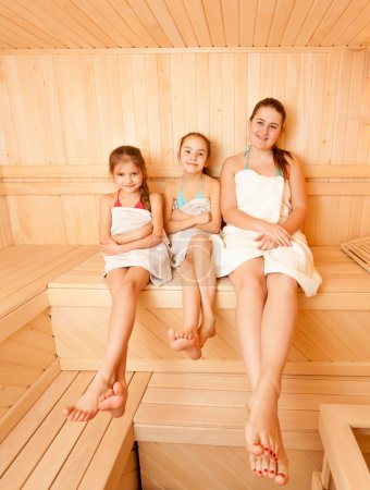 Mother with two daughter relaxing at steam bath