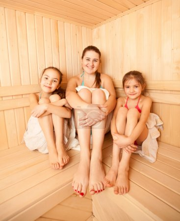 Two little girls relaxing in sauna with mother