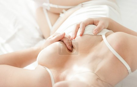 Photo of woman holding hands on breast in corset at  bed