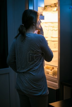 young woman looking inside the fridge at late night