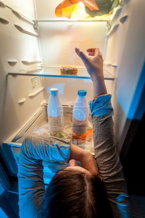 woman taking donut from top shelf of refrigerator