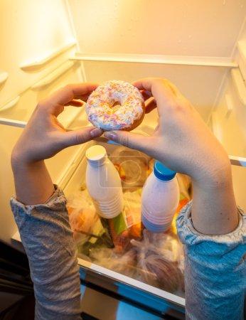 hands taking big donut from top shelf of fridge