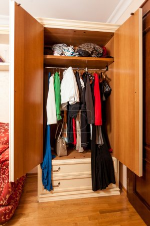 photo of wardrobe with clothes on hangers in it