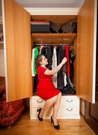 Photo for Beautiful elegant woman looking at dresses in big wardrobe - Royalty Free Image