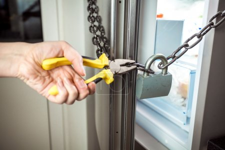 Photo for Closeup photo of woman cutting chain on fridge with pliers - Royalty Free Image
