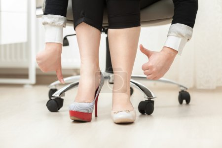 Woman wearing high heel shoe and ballet flat holding thumbs down