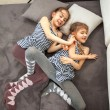 Two young sisters fighting on bed...
