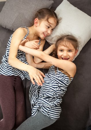two young sisters pushing each other on bed
