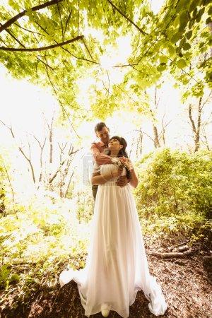 Photo pour Photo tonique de beau couple nouvellement marié embrassant sous l'arbre à la journée ensoleillée - image libre de droit