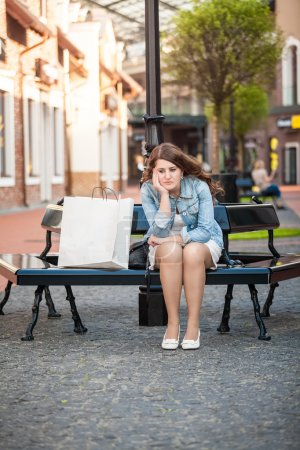 sad woman sitting on bench with shopping paper bag