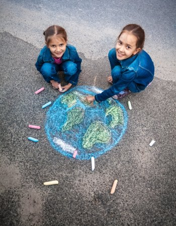 smiling girls drawing Earth with chalks on street