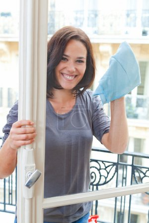 Young woman cleaning windowpane