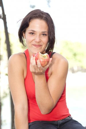 Young woman smiling, with apple