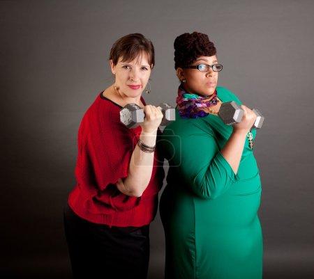 """Photo pour Confiant, graves et les femmes de la taille de différentes races à la recherche à la caméra porter """"BOLD"""" couleurs haltères tenue dénotant la puissance de l'entreprise - image libre de droit"""