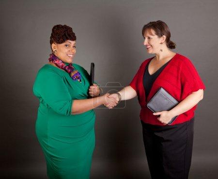 Photo pour Heureux, souriant et les femmes de la taille de différentes races se serrant la main détenant un portefeuille d'affaires - image libre de droit