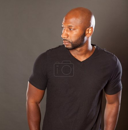 Photo pour Young athletic black man in a casual pose wearing a dark t shirt looking away from the camera with a sesios attitude expression looking to the side - image libre de droit