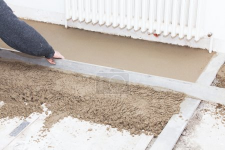 mason leveling the cement screed