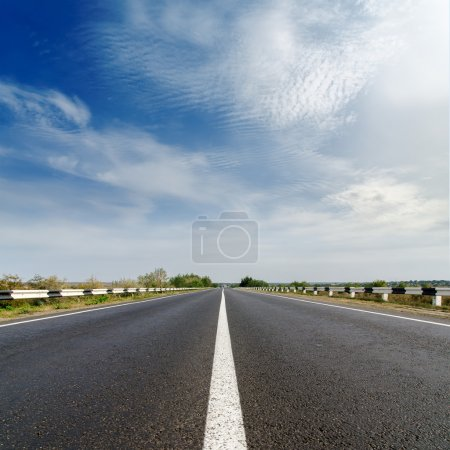 Photo for Road closeup under cloudy blue sky - Royalty Free Image