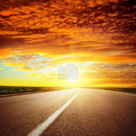 Photo pour Coucher de soleil dramatique rouge sur route asphaltée - image libre de droit
