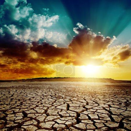 Photo pour Réchauffement climatique. coucher de soleil spectaculaire sur la terre fissurée - image libre de droit