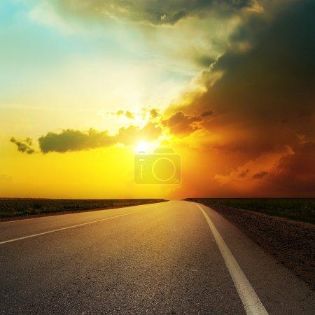 Photo pour Coucher de soleil spectaculaire sur route asphaltée - image libre de droit