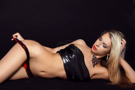 Sexy woman striping black lingerie over black background. Tempta