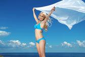 Portrét mladé ženy cítit se svobodný proti modré obloze s blowi