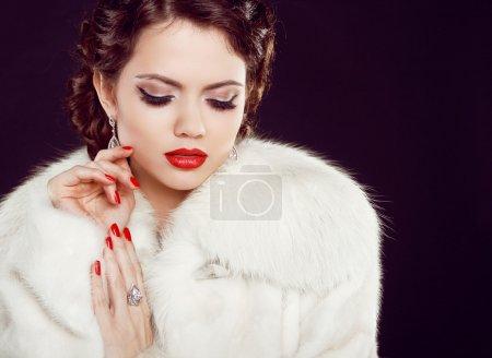 Photo pour Portrait glamour du modèle de la belle femme en manteau de fourrure de luxe sur noir - image libre de droit