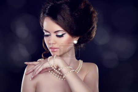 Glamour portrait of beautiful woman with pearl necklace on the b