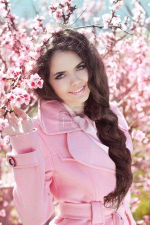Photo pour Belle fille brune avec des cheveux tressés sur arborescence de fleur rose, portrait en plein air - image libre de droit