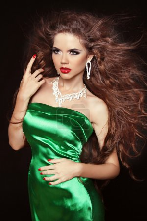 Beautiful elegant woman with long curly hairs in elegant dress p