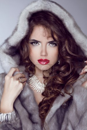 Fashion sexy model girl with red lips posing in Mink Fur Coat. W