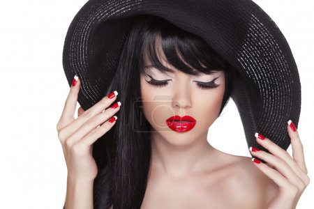 Photo pour Beauté mode sexy fille portrait en chapeau noir. lèvres rouges et vernis ongles manucurés. attrayant modèle mignon avec les cheveux longs isolés sur fond blanc . - image libre de droit