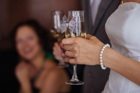 Photo pour Lunettes avec champagne dans les mains des mariés. Profondeur de champ faible - image libre de droit