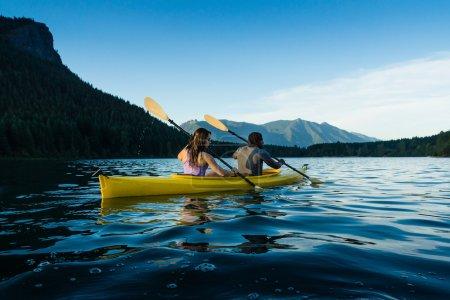 Photo for Couple paddling in kayak on lake. - Royalty Free Image