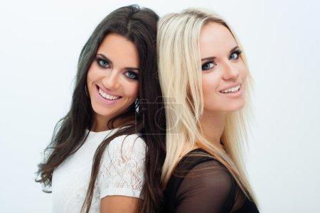 Photo pour Deux petites amies heureuses posant sur fond gris - image libre de droit