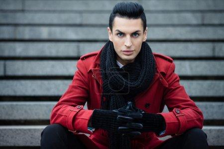 Photo pour Modèle masculin à la mode posant à l'extérieur en manteau rouge et écharpe noire - image libre de droit