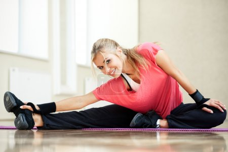 Photo for Smiling athletic woman stretches the muscles in a gym - Royalty Free Image