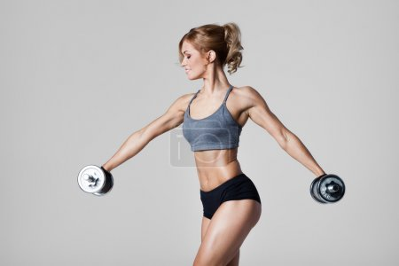 Photo for Smiling athletic woman pumping up muscules with dumbbells on gray background - Royalty Free Image