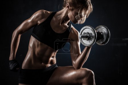 Photo for Brutal athletic woman pumping up muscules with dumbbells - Royalty Free Image