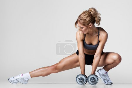 Photo for Smiling athletic woman pumping up muscules with dumbbells and stretching legs - Royalty Free Image
