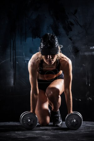 Photo for Sexy woman in a cap with dumbbells on dark background - Royalty Free Image