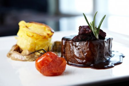 Photo for Roasted beef tenderloin with herb-potato muffin, mushroom ragout, baked tomatoes and rosemary-currant sauce - Royalty Free Image