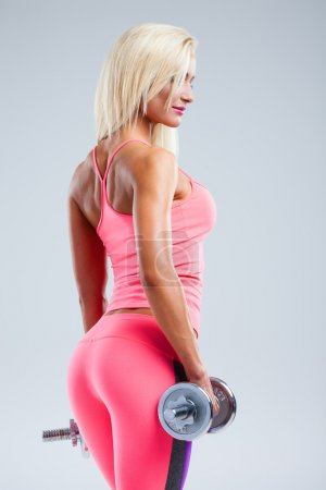 Beautiful fitness model posing with dumbbells on g...
