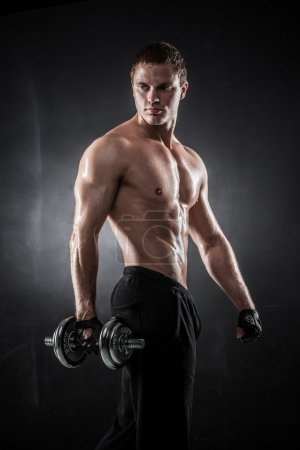 Photo for Handsome athletic man pumping up muscles with dumbbells - Royalty Free Image