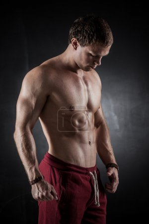 Photo for Handsome athletic man posing on dark background - Royalty Free Image