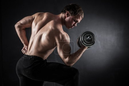 Photo for Brutal athletic man pumping up muscles with dumbbells - Royalty Free Image
