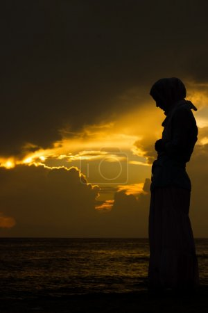 Young muslim woman praying at sunset...