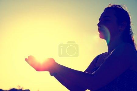 Photo pour Silhouette de femme tenant le soleil - image libre de droit