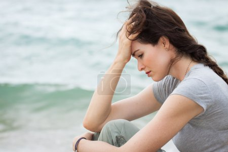 Photo for Close-up of a sad and depressed woman deep in though outdoors. - Royalty Free Image